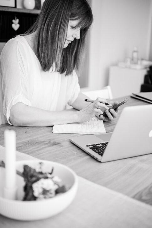 Frau tippt in Handy in schwarz weiß bei Businessfotografie Celle