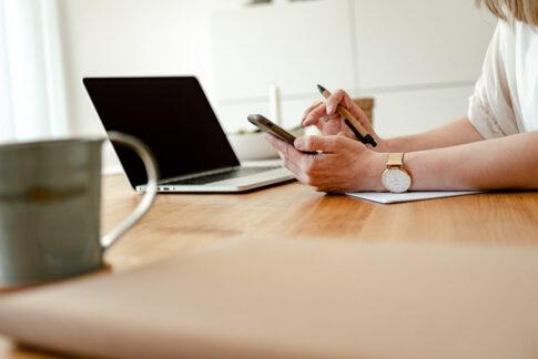 Arbeitend am schreibtisch. Man sieht nur die Hände, die ins Handy tippen. Alles in nordisch hell dekoriert