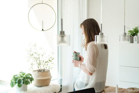 Frau steht mit Kaffee am Fenster bei einem Businessportrait in Celle von Lisa von Rekowski Fotografie