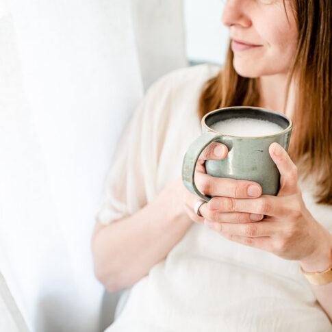 Frau hält Kaffeebecher in der Hand und schaut entspannt aus dem Fenster. Man erkennt sie nicht. Businessfotografie Celle