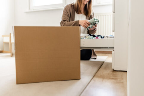 Im Vordergrund ein Umzugskartondahinter räumt eine Frau Wäsche in Schublade