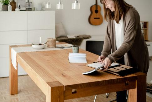Frau sotiert Unterlagen auf Schreibtisch, dabei lächelt sie. Businessfotografie Celle