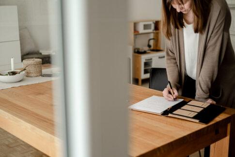 Frau notiert etwas in ihren Unterlagen an Esstisch. Das Wohnzimmer ist hell und klar. Businessfotografie Celle
