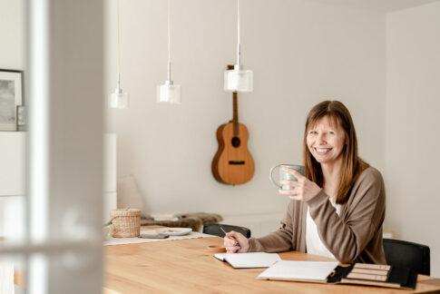 Ordnungscoach Michaela Pieper lächelt am Esstisch sitzend in die Kamera, bei Businessshooting in Celle
