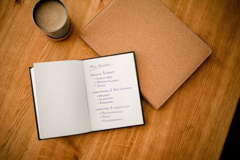 Notizen neben Kaffee auf Tisch
