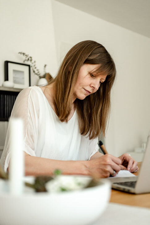 Frau schreibt etwas auf. im Hintergrund skandinavisches Dekor bei einem Businessporträt in Celle