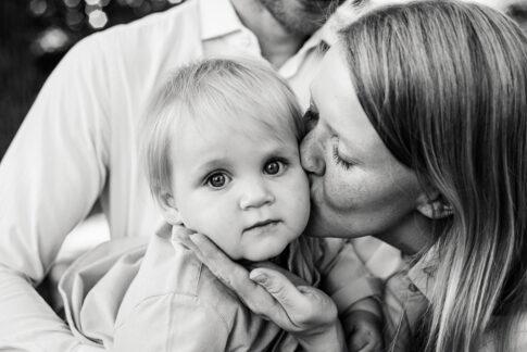 Mutter küsst Kleinkind auf Wange bei Familienshooting in Celle