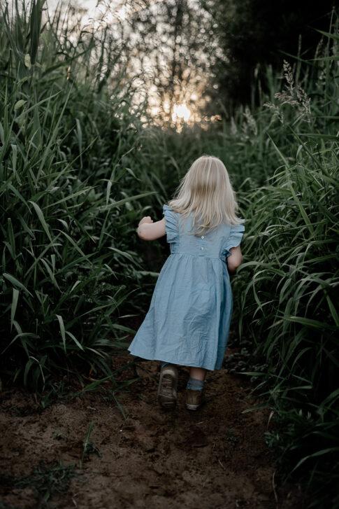 Mädchen läuft durchs hohe Gras an der Aller in Celle