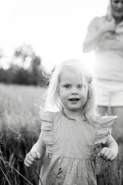 kleines Mädchen in schwarz weiß im Gegenlicht auf den Allerwiesen bei Familienshooting in Celle