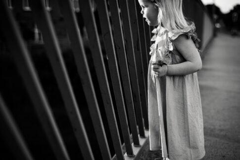 kleines Mädchen steht an Brückengeländer in schwarzweiß bei Familienshooting in Celle