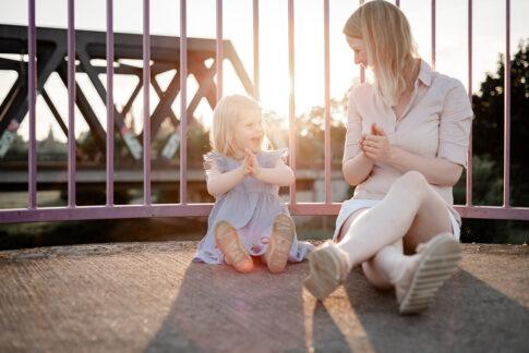 Mutter und Tochter sitzen vor Brückengeländer im Gegenlicht und klatschen in die Hände bei Familienshooting in Celle