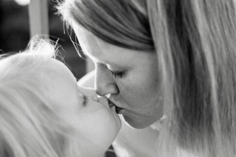Mutter gibt Tochter einen Kuss bei Familienshooting in Celle