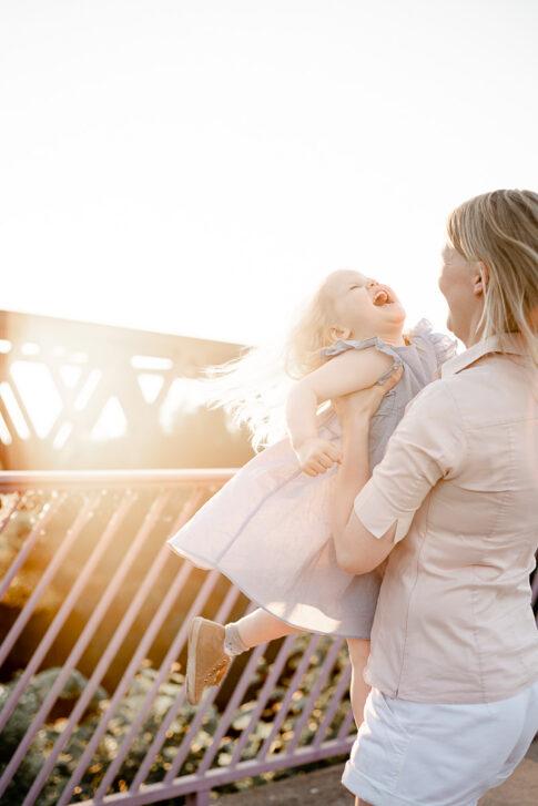 Mutter wirbelt Tochter in der Luft im Gegnlicht bei Familienshooting in Celle