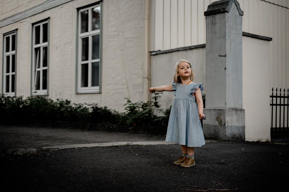 Mädchen steht vor Toreinfahrt und zeigt bestimmt in diese Richtung bei Familienshooting in Celle