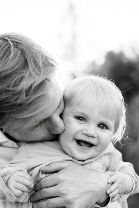 Vater gibt Kleinkind einen Kuss, dabei lacht das Kind. Familienfotografie in Celle