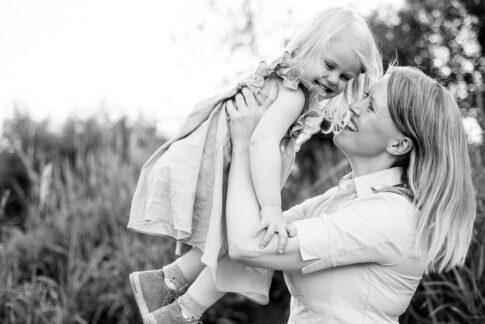 Mutter wirft Tochter in die Luft beim Familienshooting an der Aller in Celle