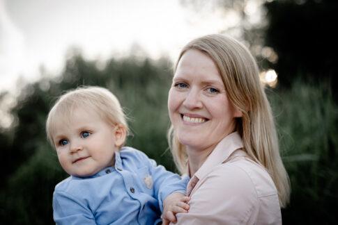Mutter lächelt beim Familienshooting in die Kamera. An der Aller in Celle