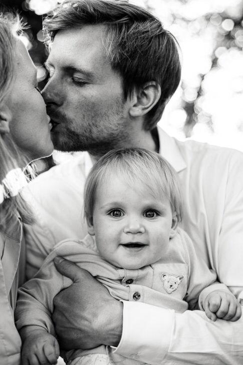 Vater und Mutter küssen sich. Auf Arm der Kleine Sohn bei Familienportraitaufnahmen in Celle