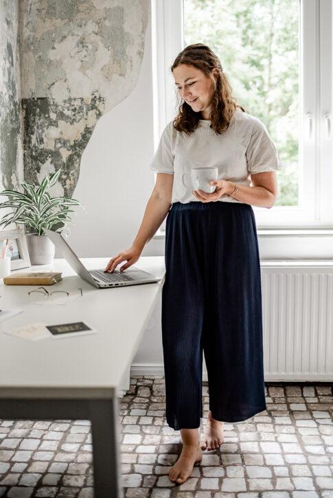 Frau steht an Schreibtisch entspannt mit Kaffeebescher in der Hand. Bilder für Businesspoträts in Celle