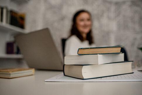 Junge Unternehmerin sitzt hinter Bücherstapel und PC , bei Businessshooting in Celle