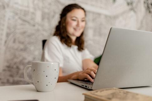 Frau lächelt beim arbeiten in Richtung ihres PC´s , die Kaffeetasse steht im Vordergrund. Bei einem Businessshooting in Celle
