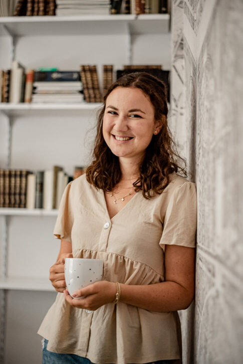 Junge Frau mir Kaffeebecher in der Hand an Wand im Büro angelehnt bei Businessshooting in Celle