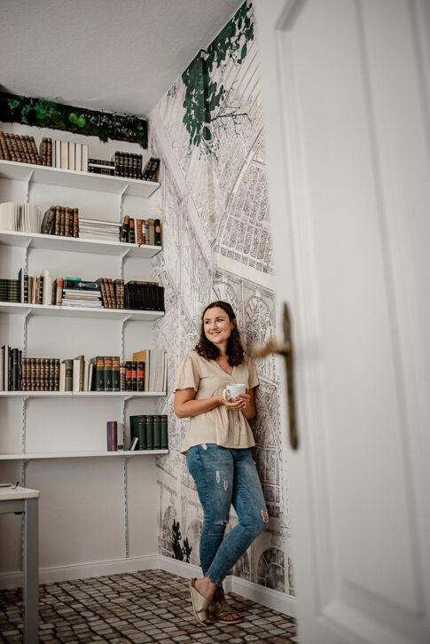 Frau lehnt an Wand mit Kaffeebecher in der Hand bei einer Businessreportage in Celle