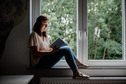 Frau sitzt auf Fensterbank und liest ein Buch. Bei einer Businessfotoreportage in Celle entstanden.