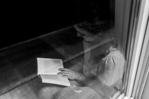 Frau liest ein Buch durch Fenster fotografiert in schwarzweiß. Businessshooting in Celle