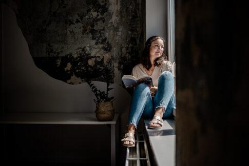 Frau sitzt entspannt am Fenster mit Buch in der Hand. Aufgenommen bei einem Businessshooting in Celle.