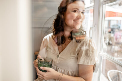 Frau an Fenster mit Teetasse in den Händen. Bei Fotoshooting in Celle