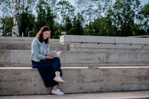 Frau sitzt auf Treppen am Celler Hafen und liest. Bei Businessshooting in Celle