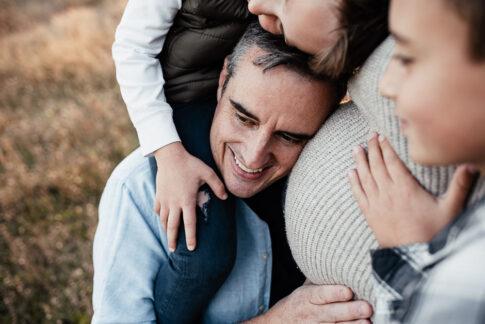 Vater mit Sohn auf Schultern lehnt an Babybauch der Mutter mit seinem Kopf bei Familienshooting in Wolfsburg