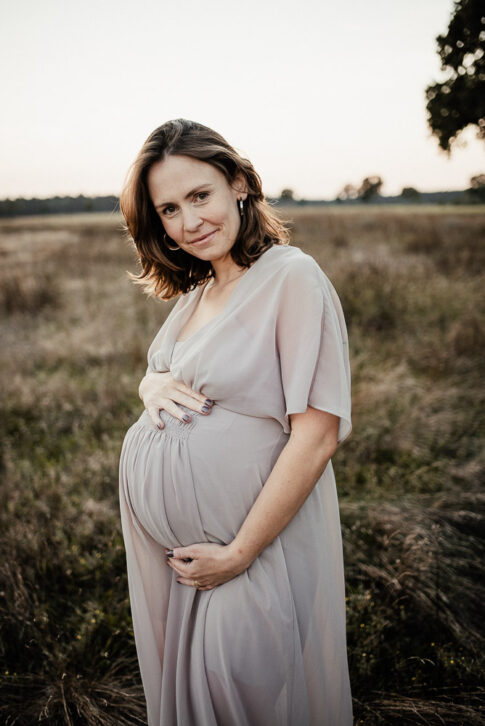 Schwangere Frau im rosafarbenen Shootingkleid bei Abendlicht während eines Babybauchshootings in Wolfsburg