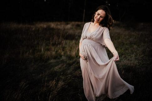 schwangere Frau tanzt im Kleid auf Wiese während eines Babybauchshootings in Wolfsburg