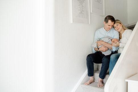 Eltern mit Neugeborenen auf Treppe bei Newbornshooting in Celle, Hannover