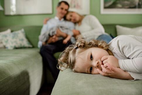 Im Vordergrund kleines Mädchen im Hintergrund verschwommen die glücklichen Eltern mit Baby bei Familienfotografie in Celle, Hannover